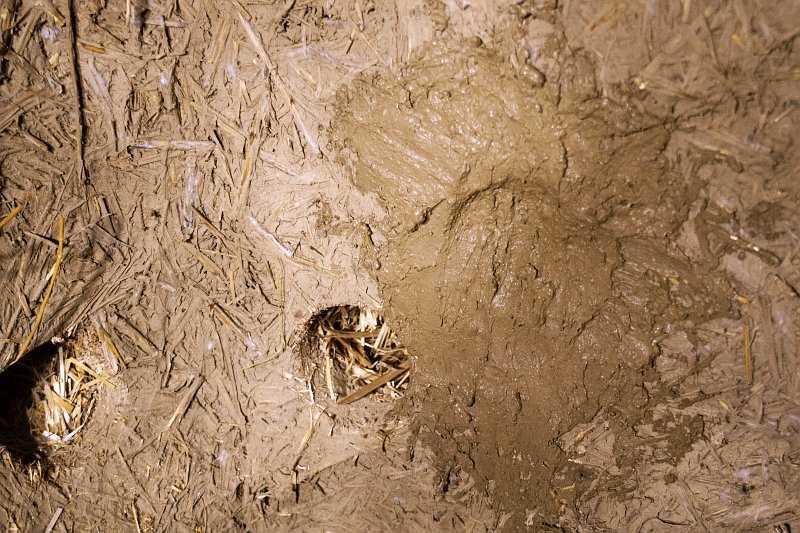 otwór w ścianie ze słomy wypełnony gliną